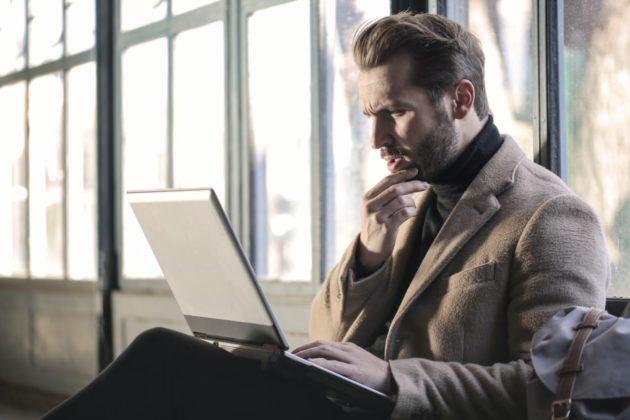 man thinking while looking at his computer